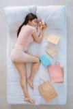 Joyful nice woman sleeping with a present Stock Images