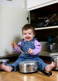 Joyful Noise 1. Adorable baby girl banging on pots and pans in the kitche Royalty Free Stock Photos