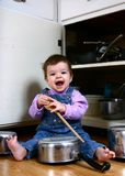 Joyful Noise 2. Adorable baby girl banging on pots and pans in the kitche stock image