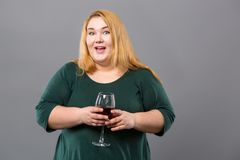 Joyful obese woman enjoying wine. Alcoholic drink. Joyful obese woman smiling while enjoying her wine Royalty Free Stock Image