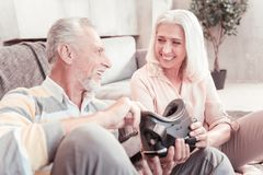 Joyful occupied couple holding VR glasses and communicating. Lets taste this. Joyful occupied satisfied couple sitting in the bright room holding VR glasses and Royalty Free Stock Photos
