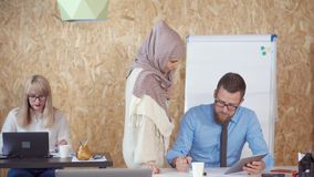 Muslim woman is standing near table of her colleague man in office and talking stock video footage