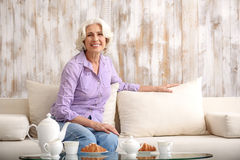 Joyful old lady resting on couch Royalty Free Stock Photos