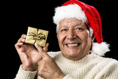 Joyful Old Man Gesturing At Wrapped Golden Gift. Male pensioner with a gentle smile is pointing at a small, wrapped, golden present held up in his right hand Royalty Free Stock Images
