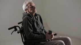 A Gray Haired Man in a Wheelchair Listens to Favorite Music with Headphones. stock video footage