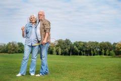 Joyful old married couple playing badminton royalty free stock images