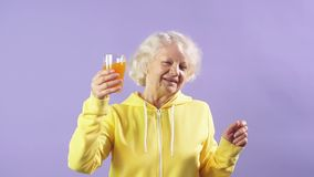 Joyful old woman in a yellow sports sweatshirt holds a glass of fresh carrot juice in her hand.  stock video