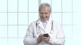 Joyful older doctor using his smartphone. Happy senior doctor in white coat answering on message on his cell phone, abstract window background stock video
