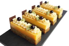 Joyful orange mousse and pistachio sponge cake slices with piped buttercream and fresh black currants royalty free stock images