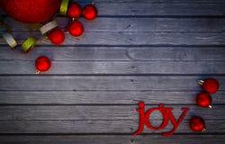 Joyful Ornaments. Red joy and ball ornaments on grey wood background royalty free stock photo