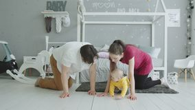 Joyful parents crawling together with baby indoors stock video footage