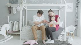 Joyful parents playing with baby girl in bedroom stock video