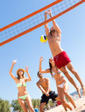 Joyful people playing volleyball on beach Royalty Free Stock Photography