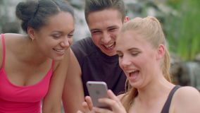 Joyful people using phone outdoor. Cheerful friends watching photos on phone stock footage