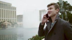Joyful phone talk during a fountain show stock video footage