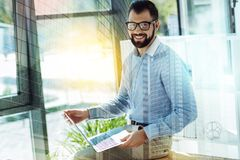 Joyful pleasant man looking straight ad smliling. Satisfied employer. Young joyful pleasant man sitting in the room on the table keeping the laptop looking Stock Images