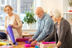 Joyful pleasant people enjoying their creative activity. Gift packing. Joyful pleasant people having fun while enjoying their creative activity royalty free stock photo