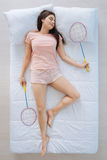 Joyful pleasant woman holding badminton rackets. Professional player. Joyful pleasant attractive woman holding badminton rackets and playing badminton while Stock Photo