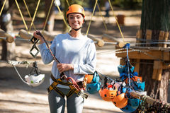 Joyful pleasant woman preparing for climbing. Think about your safety. Pleasant delighted positive woman holding a mountain carabiner and smiling while standing stock photo