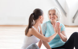 Joyful pleasant women doing high five. Give me the high five. Cheerful active confident women doing high five and laughing while relaxing after aerobics classes Stock Photo