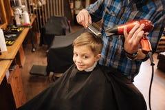 Joyful positive boy having a new hairstyle done Royalty Free Stock Photos