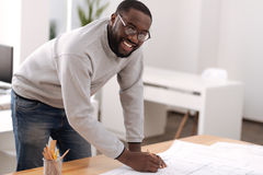 Joyful positive man doing a draft. Modern architecture. Joyful positive afro american man standing near the table and doing a draft while working as an architect Royalty Free Stock Images