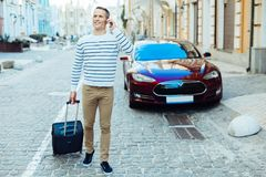 Joyful positive man holding a suitcase Stock Image