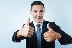 Joyful positive man showing thumbs up gestures Stock Photos