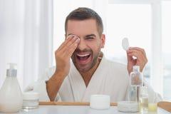 Joyful positive man using a cotton pad stock image
