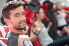 Joyful positive man working out in gym Royalty Free Stock Images
