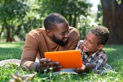 Joyful positive nice man using modern technology. New tablet. Joyful positive men using modern technology while resting on the grass in the park royalty free stock photos