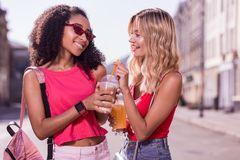 Joyful positive nice woman giving her drink to the friend Stock Images