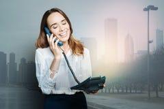 Joyful positive woman holding a phone receiver Stock Image
