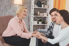 Joyful positive woman smiling to her sons wife. Welcome to family. Joyful positive women smiling to his sons fiancee while holding her hand Royalty Free Stock Images