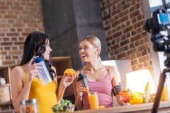 Joyful positive women making orange juice Stock Image