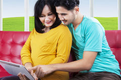 Joyful pregnant couple using tablet Royalty Free Stock Photo