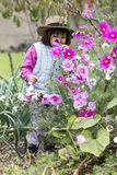 Joyful preschooler enjoying smelling organic flowers in home garden Royalty Free Stock Photography