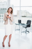 Joyful pretty businesswoman using her mobile phone Stock Images