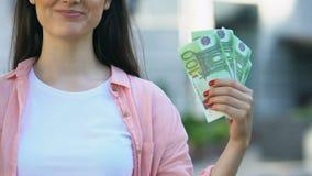 Joyful pretty female holding euro banknotes, bank deposit, cash back service stock video footage