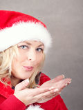 Joyful pretty woman blowing in red santa claus hat Stock Photography