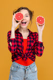 Joyful pretty woman covered one eye with half of grapefruit Royalty Free Stock Images