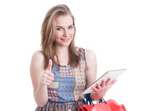 Joyful pretty woman do buyings online and thumb up. With shopping bags isolated on white studio background royalty free stock photos
