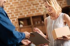 Joyful pretty woman receiving a parcel Royalty Free Stock Photos