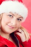 Joyful pretty woman in red santa claus hat smiling Royalty Free Stock Photography