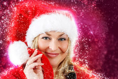 Joyful pretty woman in red santa claus hat smiling Royalty Free Stock Images