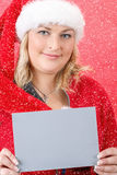 Joyful pretty woman in red santa claus hat smiling with snowflakes Royalty Free Stock Images