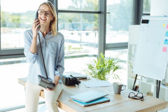 Joyful pretty woman talking on the landline phone in office. Important call. Charming upbeat woman sitting on the table in the office and talking on the landline Stock Image