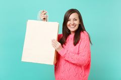 Joyful pretty young woman in knitted pink sweater hold in hand shopping bag with sale written text inscription isolated stock photos