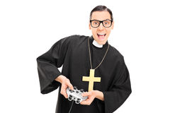 Joyful priest holding a gamepad Royalty Free Stock Photo