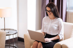 Joyful professional businesswoman working on the laptop. My favourite job. Joyful attractive professional businesswoman sitting in the armchair and smiling while Royalty Free Stock Photography